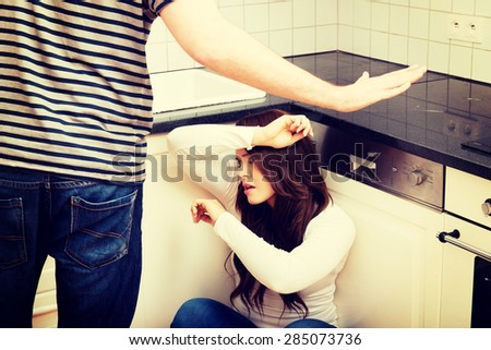 Young angry men shouting on his girlfriend in the kitchen. - stock photo