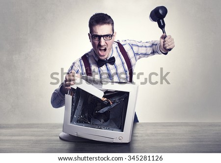 young angry nerd destroying old computer monitor - stock photo