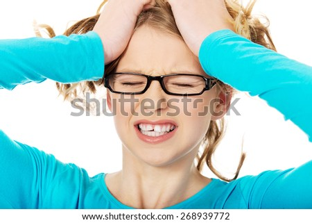 Young angry teenager pulling her hair - stock photo