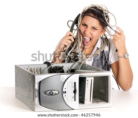 young angry woman having problems with computer and phoning helpline - stock photo