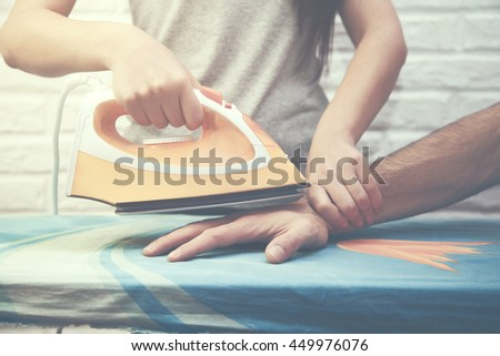 Young angry woman ironing man hand