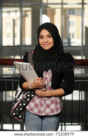 Young Arab Student holding a copybook and wearing her traditional veil - stock photo