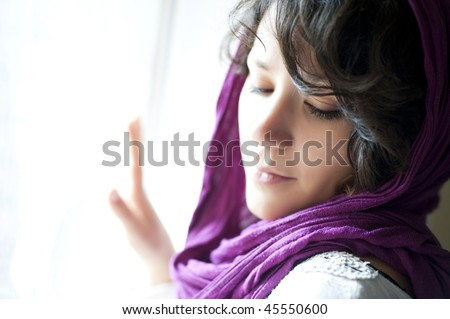 Young arab woman confined in her house wearing purple headscarf. - stock photo