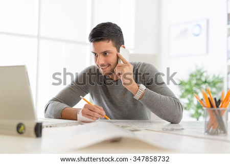 Young arabian male contractor sitting at desk in office, using phone and analyzing blueprint. He looking at the laptop in front him. - stock photo