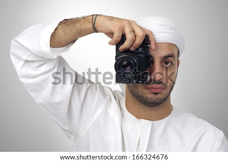 Young Arabian man using holding his camera ready to shoot, isolated - stock photo
