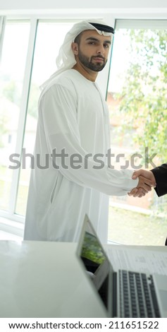Young Arabic business man hand shaking for new contract - stock photo