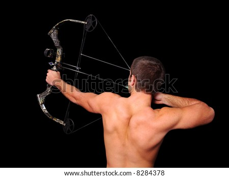 Young archer with bow and arrow aiming high isolated over a black background. - stock photo