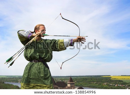 Young archer with bow and arrows in medieval costume aiming - stock photo