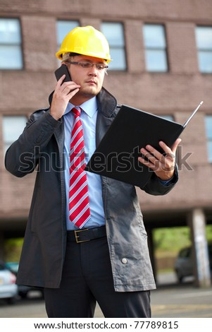 young architect or inspector with office building as blurred background