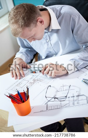 Young architect studying his project by magnifying glass - stock photo