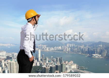 Young architect wearing a protective helmet looking the city building outdoor background - stock photo