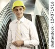 Young architect wearing a protective helmet standing on the building outdoor background - stock photo