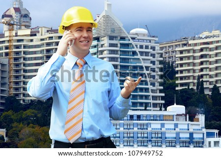 Young architect wearing a protective helmet standing on the mountains building outdoor background - stock photo