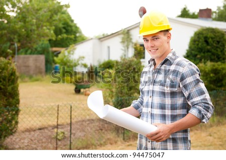 Young architect with plan in front of a building - stock photo