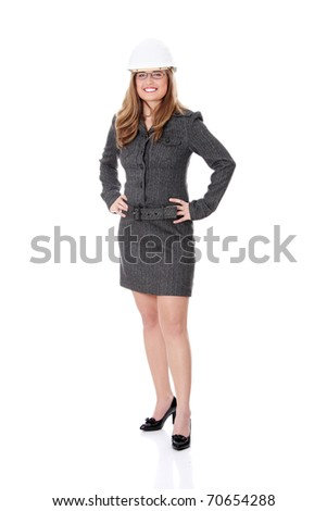 Young architect woman wearing a protective helmet, standing. Isolated on white background - stock photo