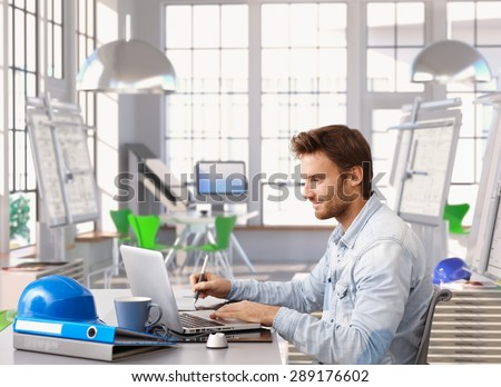 Young architect working at office desk using laptop and digital drawing table.