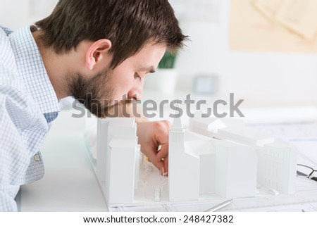 Young architect working on a architectural model