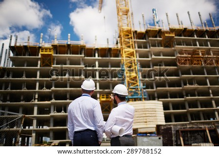 Young architects consulting about new construction at meeting outdoors - stock photo