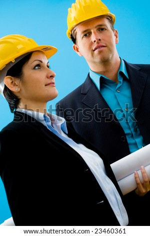 Young architects in yellow hardhat against blue background. - stock photo