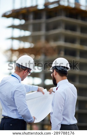 Young architects looking at blueprint with sketch of construction - stock photo