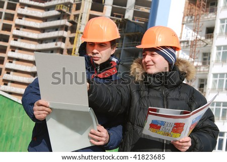 Young architects wearing a protective helmet standing in front of a building site - stock photo
