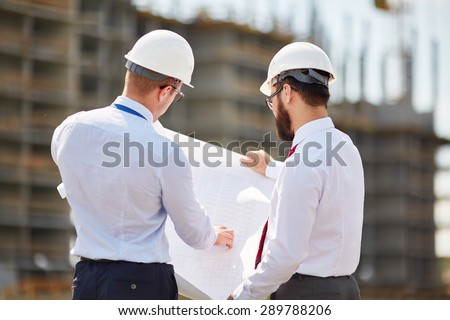 Young architects with blueprint discussing sketch of new building construction - stock photo