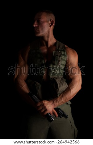 Young armed serious soldier in uniform standing proud against black background. War on terror.  - stock photo