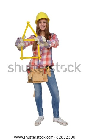 Young artisan builds a house of a yellow ruler - stock photo