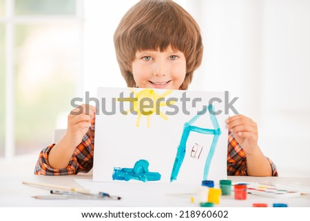 Young artist. Cheerful little boy relaxing while painting with watercolors sitting at the table - stock photo