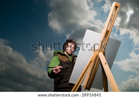 Young artist drawing outdoors over dramatic sky background - stock photo
