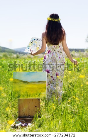 Young artist girl is create picture of a yellow flower field, spring time - stock photo