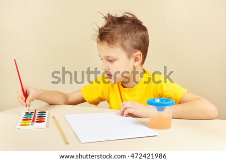 Young artist in a yellow shirt going to paint colors