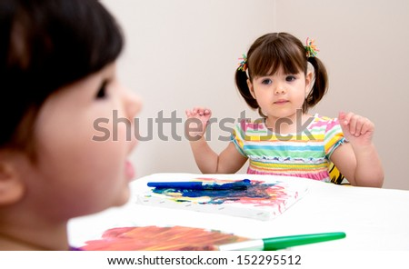 Young artist looks to her sister for painting advice - stock photo