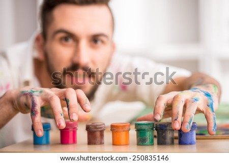 Young artist with paints. Close-up. Focus on paints.