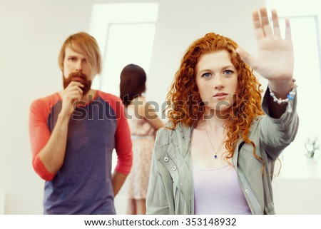 Young artists in gallery hanging together painting on walls - stock photo