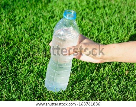 young asia girl hand get  plastic bottle from glass backgrounds