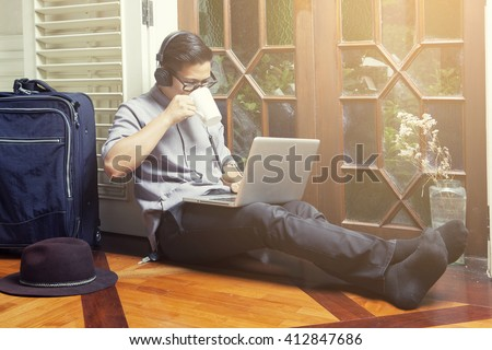 Young Asia man enjoying Drinking coffee and laptop computer while sitting in the house offfice the bed. and Cross process filter and soft flare - stock photo