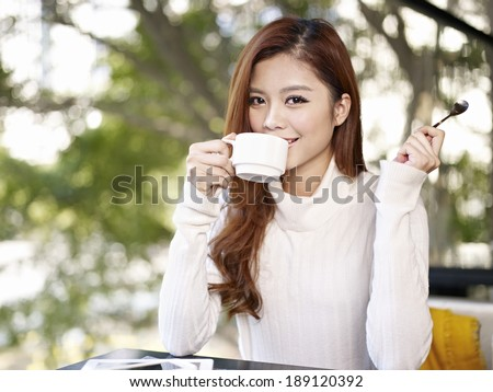 young asian adult woman drinking coffee smiling in cafe. - stock photo