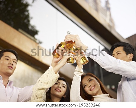 young asian adults toasting with beer. - stock photo