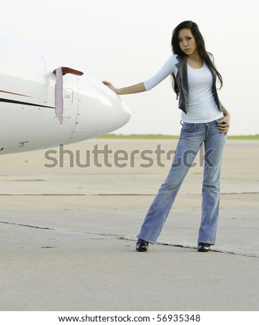 Young Asian-American woman stands leaning against nose cone of airplane on tarmac