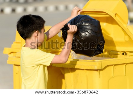 Young Asian boy carry garbage in plastic bag for eliminate in the yellow bin under the sunlight - stock photo