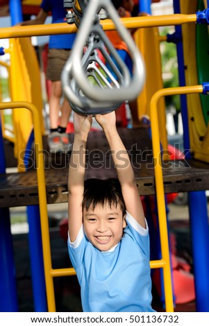 Young asian boy hang the bar by his hand to exercise at out door playground