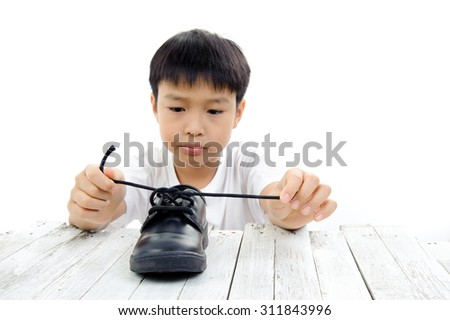 Young Asian boy lacing black leather shoe rope by his own on green tree background.