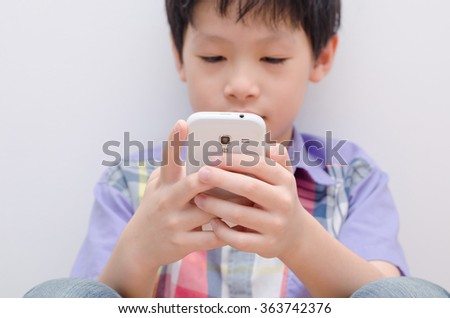 Young Asian boy play game on smart phone,focus at hand and smart  - stock photo