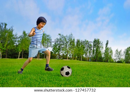 Young Asian boy playing soccer outdoors - stock photo