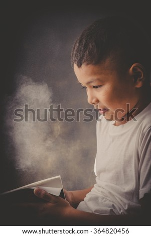 Young Asian boy reading an old book, dust, black background