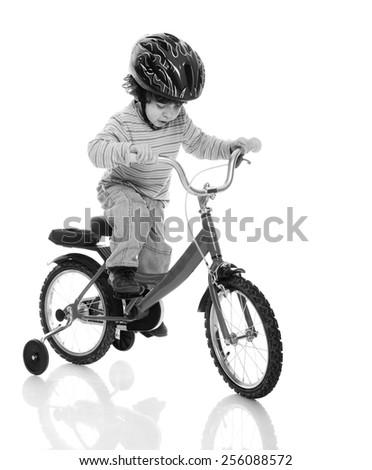 young asian boy riding on a tricycle on isolated background - stock photo