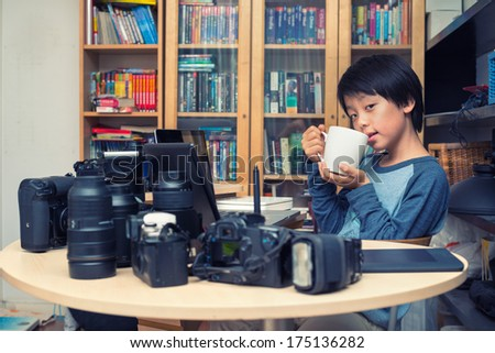 Young Asian boy taking a break during photographic work (retro look) - stock photo