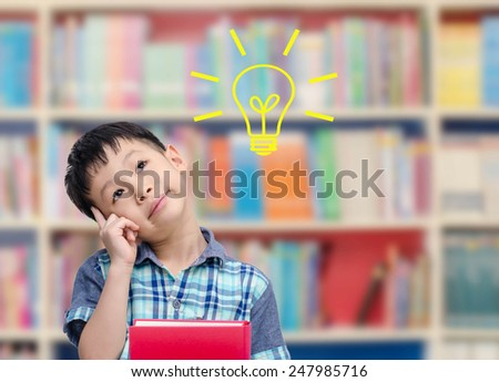 Young Asian boy thinking with bulb in library - stock photo