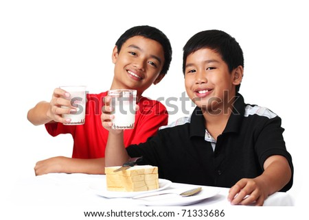 young asian boys holding glasses of milk - stock photo